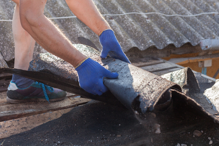 Worker demolishing old shingles to prepare a roof for a new installation