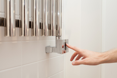 The man hand regulates thetemperature in the heated towel rail. Banco de Imagens - 98926601