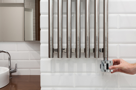 The man hand regulates thetemperature in the heated towel rail.