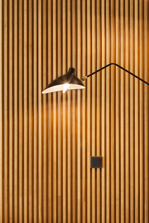 Front of modern wooden separator modern wall-mounted lamp on textured wood wall Stock Photo
