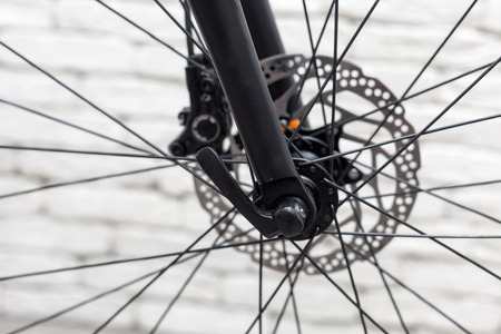 Element of a bicycle. Close up discs brakes against a white brick wall.
