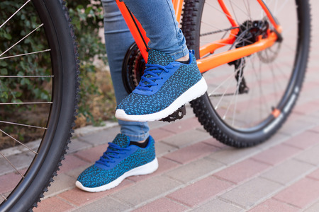 The girl put her foot on the bicycle pedal. Stock Photo