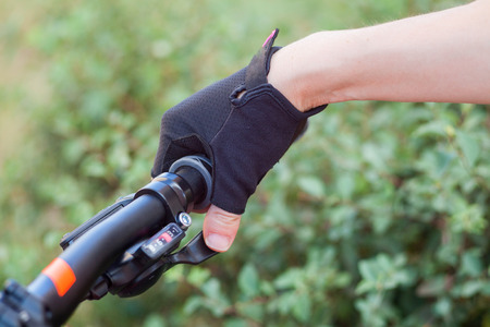 A girl in bicycle gloves holds her hand on the handlebars, clamping the brakes. Stock Photo