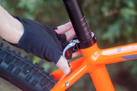 Customize the bike. A hand in bicycle gloves lowers and raises a bicycle seat. Stock Photo