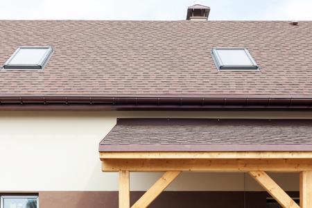 Window skylight on a roof with asphalt shingles or bitumen tiles under construction. Stock Photo