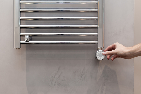 The man hand regulates the temperature in the heated towel rail in bathroom Banco de Imagens - 103853088