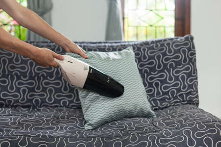 Young woman using a small manual vacuum cleaner while cleaning pillow on the couch.