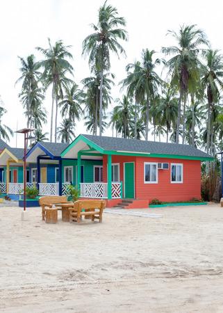 Maisons en bois multicolores sur la plage avec des palmiers et du sable blanc. Maison de vacances à l'architecture orientale avec de grandes fenêtres et la climatisation.
