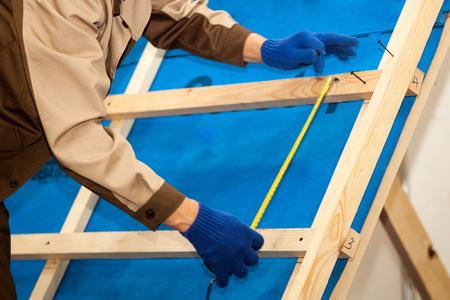 Travailleur avec perceuse électrique installation de tuiles métalliques de toit brun sur maison en bois