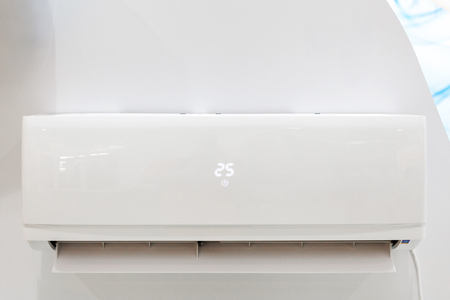 White air conditioner on a wall with temperature display and a remote control. Closeup image.