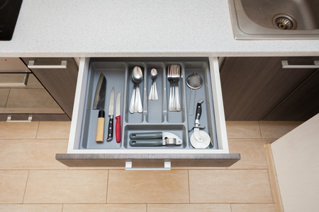 High angle top view photo of clean white cook worktop table and open new modern wooden kitchen drawer with different cutlery spoon, knife, fork and stuff Standard-Bild