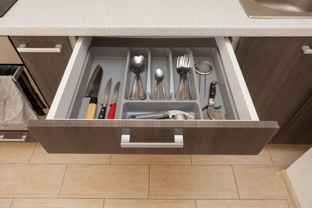 High angle top view photo of cropped part clean white cook worktop table and open new modern wooden kitchen drawer with different cutlery spoon, knife, fork and stuff