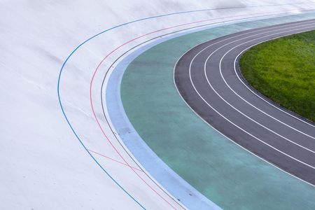 Activity, athletics concept. High angle top view cropped photo of new empty modern bicycle asphalt track in the open air with multicolored paths for playing sports Stock Photo