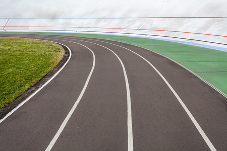 Track and field concept. High angle top view cropped photo of new modern public bicycle track or racetrack with green lawn on the open air for speed run on color market asphalt road