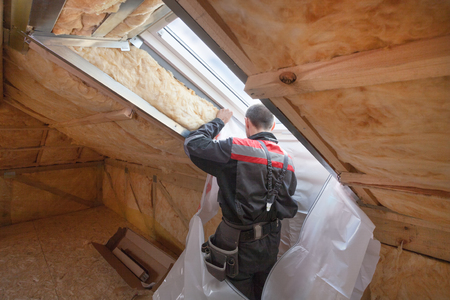 Back view of roofer builder worker installing vapor barrier around the skylight opening in attic of new house under construction