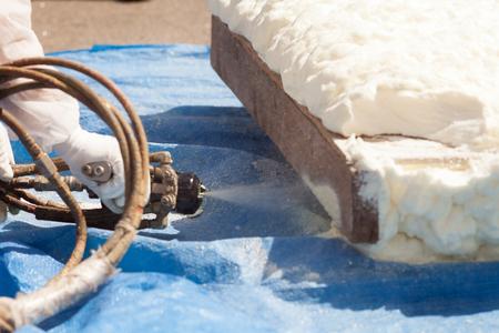 Nahaufnahme des Technikers gekleidet in einer schützenden weißen einheitlichen Sprühschaumisolierung unter Verwendung der Plural Component Spray Gun. Sprühen von Polyurethanschaum zur Dach- und Energieeinsparung