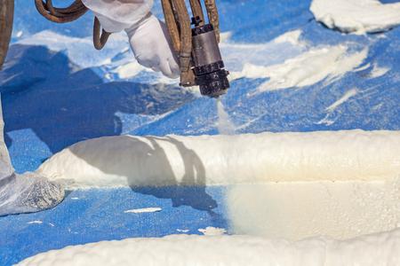 Tecnico vestito con un isolamento in schiuma di spruzzatura uniforme bianca protettiva utilizzando pistola a spruzzo multicomponente. Spruzzatura di schiuma poliuretanica per tetto e risparmio energetico Archivio Fotografico
