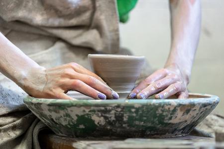 Concept de classe de maître. Photo en gros plan recadrée d'une dame de fabrication dans ses vêtements de travail sales, elle s'assoit à l'intérieur de l'espace de travail à l'aide d'une petite tasse en céramique circulaire
