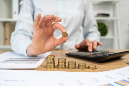 Close up cropped economist financier sale manager agent marketer lady in her formalwear she sit behind table with charts graph graphics in bright loft interior hold coin over stack focus on money
