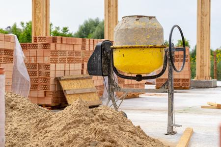 Day Lite Foto des alten gelben Rostkonzentrat-Mischers steht draußen auf dem Fundament eines unfertigen Gebäudes in der Nähe von Ziegeln und Sand
