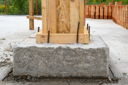 Building construction concept. Close up photo of house support element with wooden column and concrete formwork against red brick wall Stock fotó