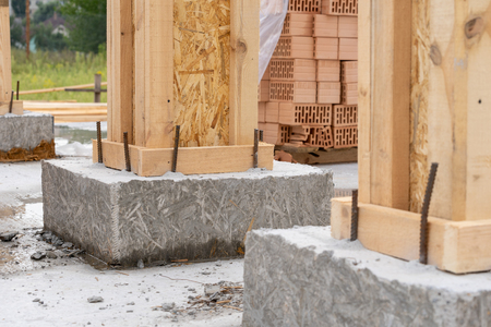 Concept of construction of new house. Close up photo of two building support element against brick wall on cement foundation Stock fotó