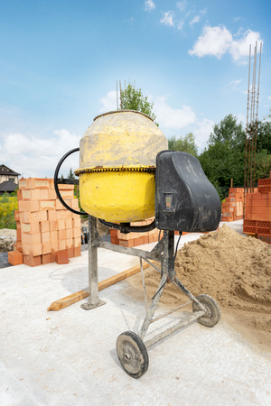 Construction of brick new home or house. Vertical day lite photo of old yellow professional concentrate mixer stand outside on the foundation of an unfinished building near brick and sand