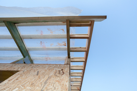 Low angle top view eaves of new wooden roof with reliable supports and windproof membrane against blue sky Stock Photo