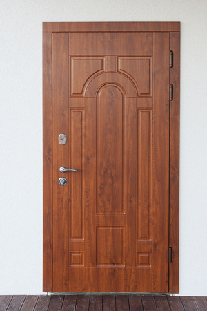 Vertical photo of beautiful metal entrance door on white plaster wall new comfort house Banco de Imagens