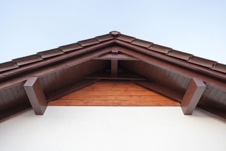 Low angle top view photo of brown roof corner  wooden elements on top of small comfortable house with white walls