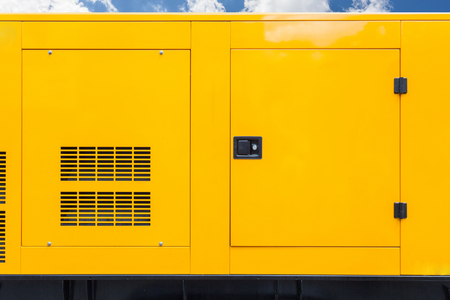 Big yellow mobile diesel box of autonomous generator for emergency electric power stand outside with blue cloud sky