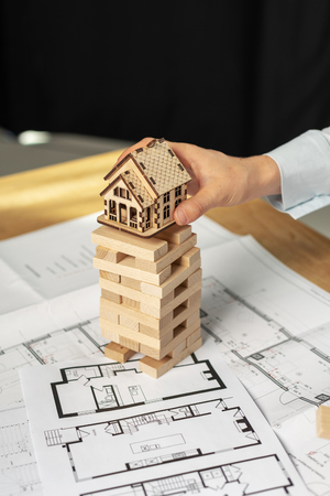 Concept of risk and building tax. Vertical photo of confident lady in her formal wear stand indoor light workplace office room, she holding little house object in hands above wooden puzzle blocks