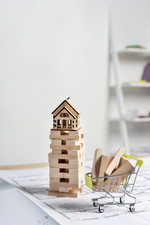 Building new flat and apartment concept. Vertical photo of small house on top of wooden blocks in little shopping cart stand on table indoor light workstation room