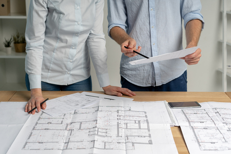Partners partnership teamwork concept. Cropped collaboration two colleagues person in formal wear shirt stand at the table in bright loft interior workplace look at blank expertise inspect property