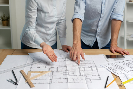 Cropped two partners specialist builder person in formalwear shirt stand in loft interior workstation hold pencil in hand indicate look at graphic make brainstorming renovation room in structure