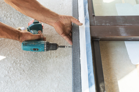 Close up cropped photo of adult handyman using torque screwdriver and assembly new plastic window frame