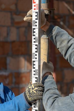 Formwork construction concept.  Cropped close up and vertical photo of cooperation between two mature specialist. They working in unfinished house tuning high of support pipe using ruler