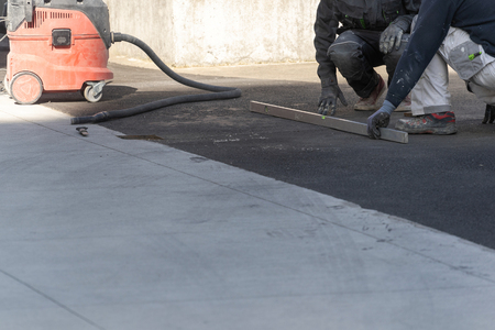 Cropped photo of two mature workman  checking level of asphalt making pavement repair or construction work