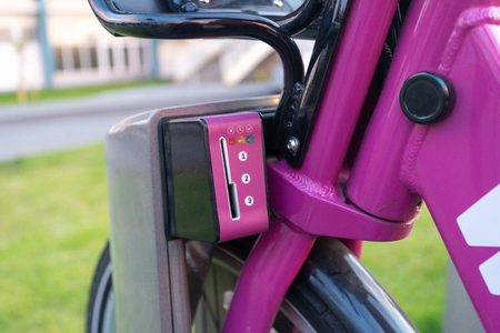 Cropped close up photo of parking of modern bicycle for rental. On picture element of payment and unlock system