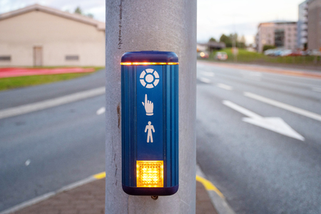 Press the button and ready to cross the street. Photo of blue traffic light with small pedestrian Stock Photo