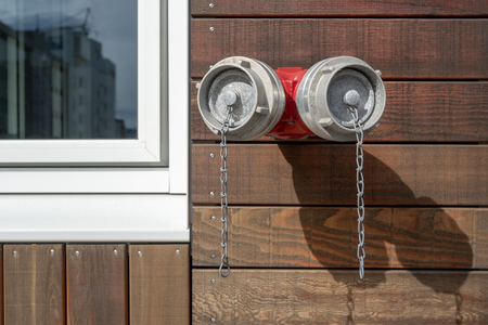 Close up photo of red fire hydrant on wall of wooden building