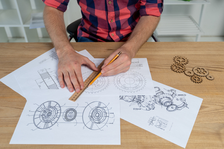 Cropped photo of focused man sitting behind wooden desk in bright light interior and drawing complicate mechanical sketch with cogwheel elements 版權商用圖片