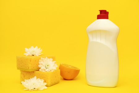 Sponge for dishes washing, white flowers and some lemons lying near bottle of cleaning soap isolated on yellow background