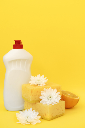 Stack sponge for dishes washing, white flowers and some lemons lying isolated on yellow background near bottle with cleaning soap