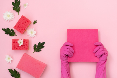 Woman holding micro fiber wipe in hands against some polyurethane sponges, white flowers and green leaves isolated on pastel pink background