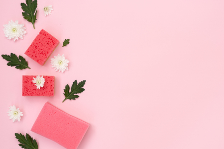 High angle top view of some polyurethane sponges, white flowers and green leaves laying isolated on pastel pink background with empty space for text