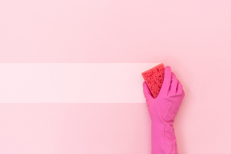 Woman holding polyurethane dish sponge for washing in hand isolated on pastel pink background with empty space for text