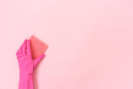 Woman in rubber gloves holding small sponge for washing in her hand isolated on pastel pink background with empty space for text