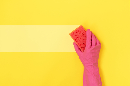 Woman holding polyurethane dish sponge for washing in hand with pink rubber gloves isolated on yellow background with empty space for text Banco de Imagens