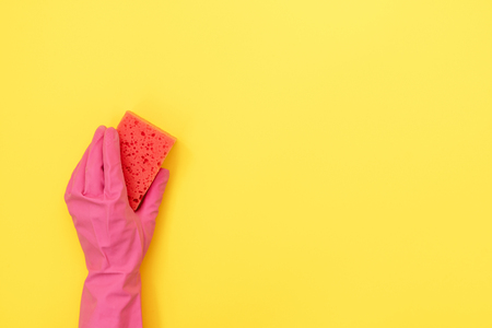 Woman in gloves holding polyurethane sponge for washing in hand isolated on yellow background with empty space for text